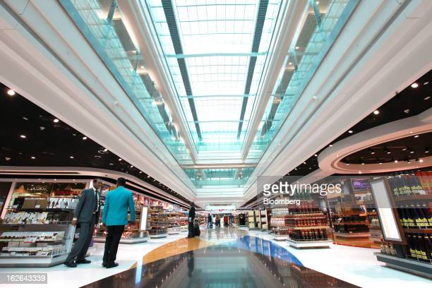 People stand alongside the Duty Free shopping area inside terminal 3 at concourse A the new A380 terminal at Dubai International Airport in Dubai...