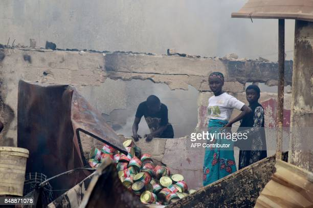 People stand amid debris in the market after a fire devastated the building during the night on September 18 2017 in Abobo neighborhood of Abidjan /...