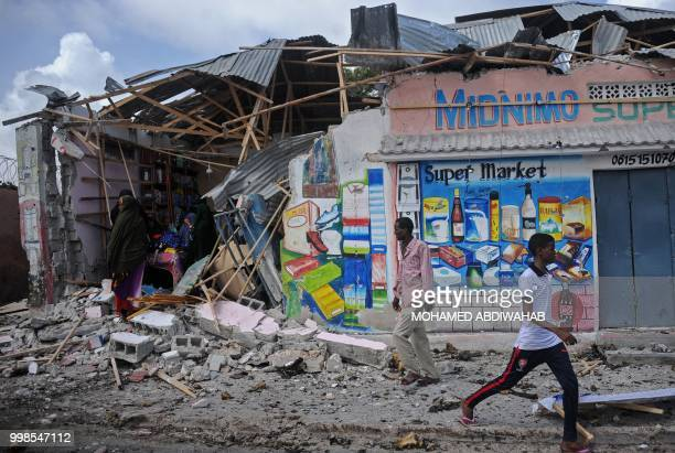 People stand amid rubble of destroyed shops after two car bombs were detonated and three Shabaab gunmen were shot dead after exchanging fire with...