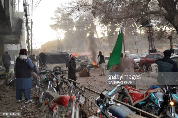 People stand amidst debris along a street following a suicide blast in Quetta on February 17 2020 At least eight people including two police officers...