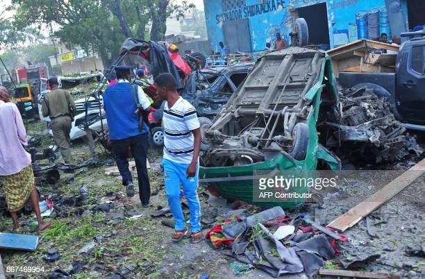 People stand among damages at the scene of a blast after two car bombs exploded in Mogadishu on October 28 2017 A car packed with explosives blew up...