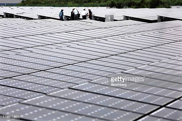 People stand among solar panels installed at the Ukishima Solar Power Plant in Kawasaki City Kanagawa Prefecture Japan on Wednesday July 27 2011 The...
