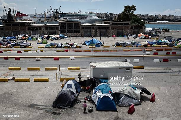 People stand among tents on May 18 2016 at the Piraeus port where some 1500 migrants and refugees live in a makeshift camps on passenger areas Greece...