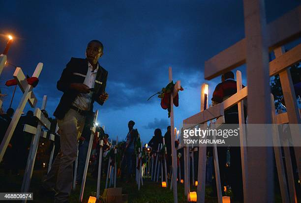 People stand among wooden crosses at FreedomCorner in Uhuru Park in Nairobi on April 7 2015 during a candlelight vigil for the victims of an attack...
