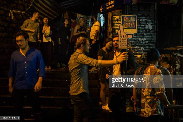 People stand and drink at Lan Kwai Fong a famous clubs street in Hong Kong on June 17 2017 in Hong Kong Hong Kong Hong Kong is marking 20 years since...