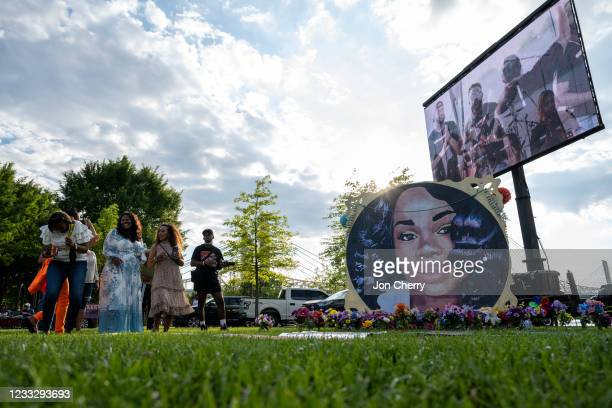 """People stand and laugh near an art installation depicting Breonna Taylor during the """"Praise in the Park"""" event at the Big Four Lawn on June 5, 2021..."""
