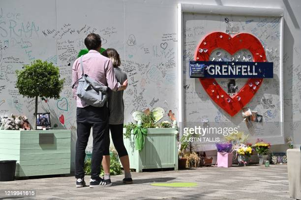 People stand and pay their respects in front of a wall where messages of support have been written surrounding Grenfell tower in west London on June...
