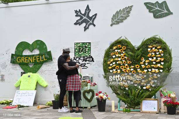 People stand and pay their respects in front of floral tributes left beside a wall where messages of support have been written surrounding Grenfell...