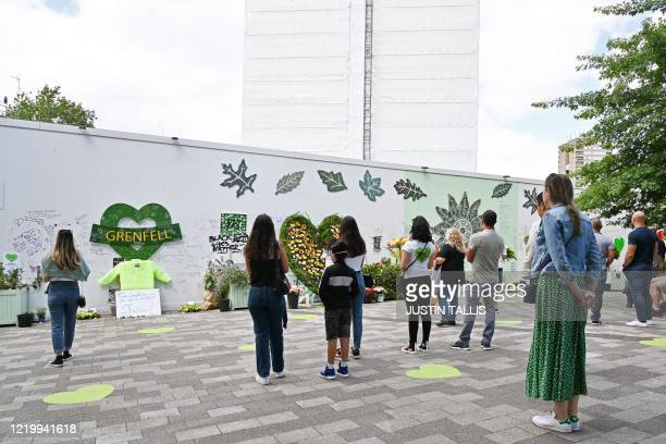 People stand and pay their respects in front of Grenfell tower covered in a safety tarpaulin in west London on June 14 on the third anniversary of...