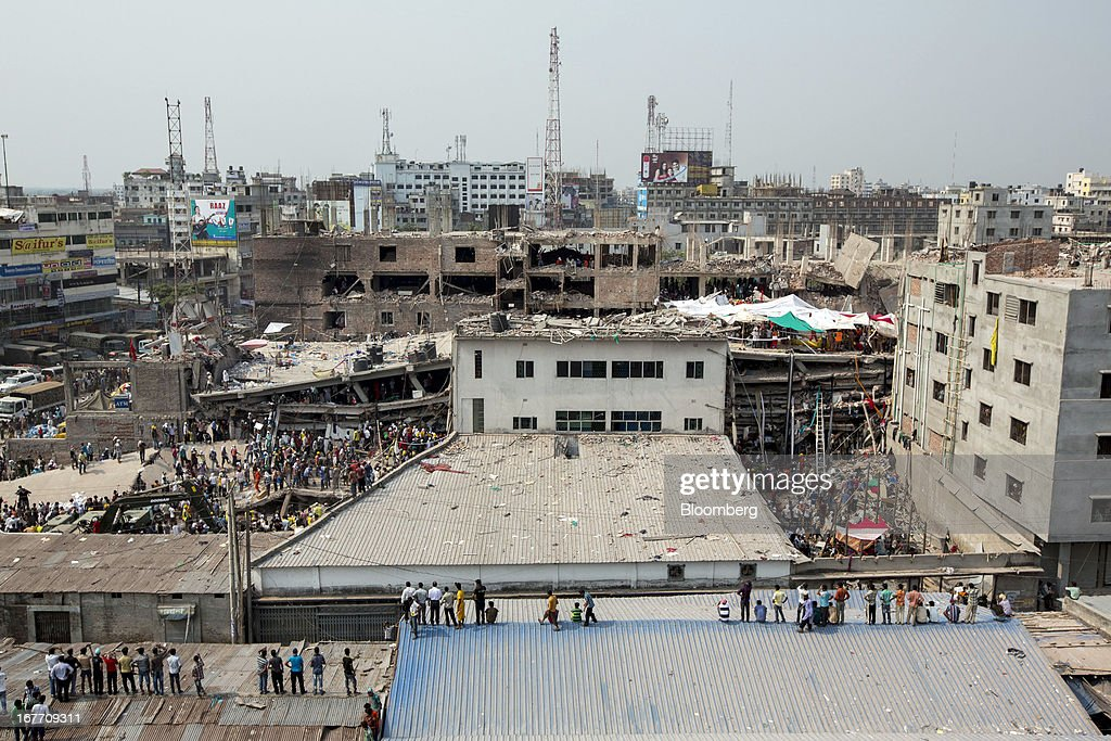 People stand and watch as rescue workers search for victims amongst the debris of the collapsed Rana Plaza building in Dhaka, Bangladesh, on Friday, April 26, 2013. The day after a Bangladesh building collapsed, killing more than 290 people, disagreement emerged over whether the owner obtained appropriate construction permits, adding to concerns over worker safety in the country's garment industry. Photographer: Jeff Holt/Bloomberg via Getty Images