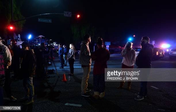 TOPSHOT People stand and watch as the scene unfurls from the intersection of US 101 freeway and the Moorpark Rad exit as police vehicles close off...