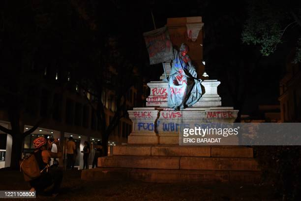 People stand around and take pictures of the statue of Confederate general Albert Pike after it was toppled by protesters at Judiciary square in...