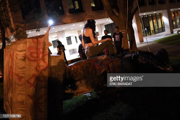 People stand around and take pictures with the statue of Confederate general Albert Pike after it was toppled by protesters at Judiciary square in...