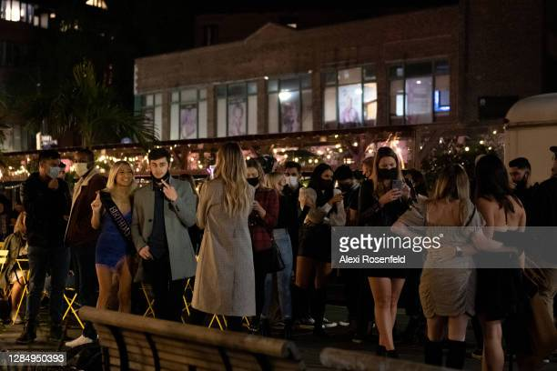 People stand around avoiding social distancing and take pictures at Baby Brasa on November 06, 2020 in New York City. The pandemic continues to...