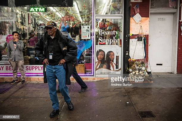 People stand around outside the beauty salon where Eric Garner was killed on July 17 by a police officer who put him in a choke hold on December 3...