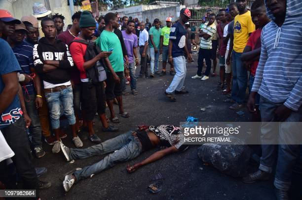 People stand around the body of a man killed in clashes with police during demonstrations on the fifth day of protests in PortauPrince February 11...