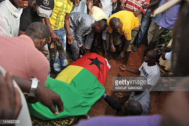 People stand around the coffin of former military intelligence chief Colonel Samba Dialloon March 20 2012 in Bissau during his funeral ceremony...
