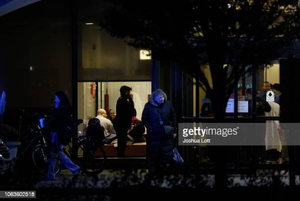 People stand around the main entrance of Mercy Hospital where a gunman shot multiple people on November 19 2018 in Chicago Illinois Three people...