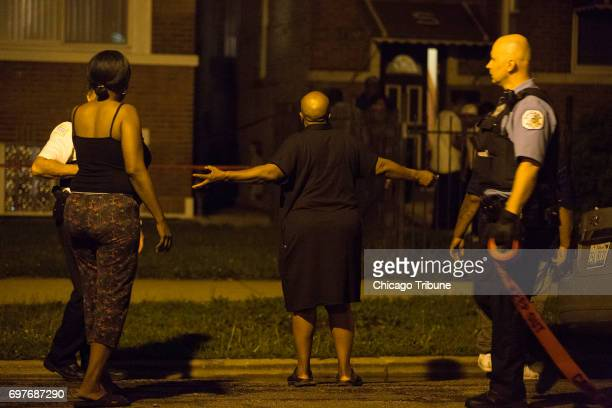 People stand around the scene where a man and woman both in their 60s were found stabbed to death in a home by a family member in the 1400 block of...