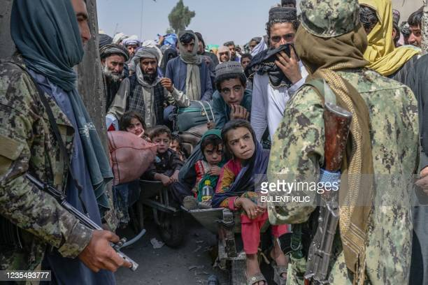 People stand as Taliban members stopped them while rushing to pass to Pakistan from the Afghanistan border in Spin Boldak on September 25, 2021. -...