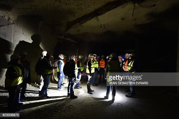 People stand as they visit a room of cabling servers in an underground datacenter on November 15 2016 near Saumur western France The underground...