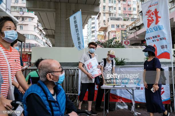 People stand at a booth where passersby can give their signatures in support of a new security law in Hong Kong on May 29 2020 China faced growing...