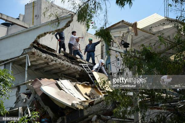 People stand at a building which collapsed after a quake rattled Mexico City on September 19 2017 A powerful earthquake shook Mexico City on Tuesday...