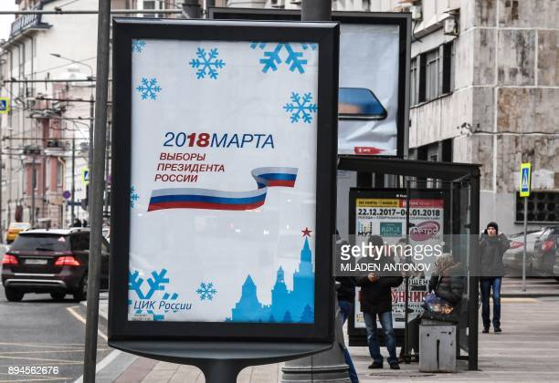 TOPSHOT People stand at a bus stop next to an official poster announcing next year's presidential election in Moscow on December 18 2017 Campaigning...