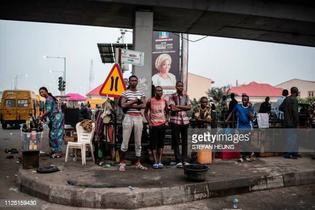 TOPSHOT People stand at a crossroad under a bridge in Lagos on February 16 2019 after Nigeria's electoral watchdog postponed presidential and...