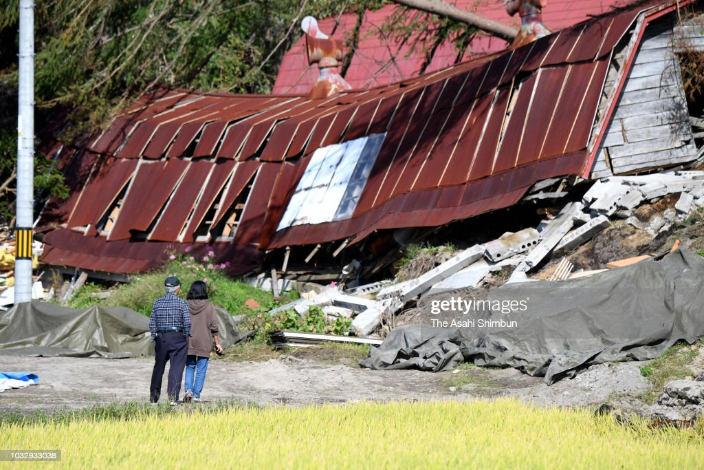 People stand at a destroyed house of their friends a week after the magnitude 6.7 earthquake on September 13, 2018 in Atsuma, Hokkaido, Japan. Concerns are rising about the health of the evacuees because prolonged life in shelters can pose serious risks. Living away from home and together with strangers puts enormous mental and physical strains on evacuees.