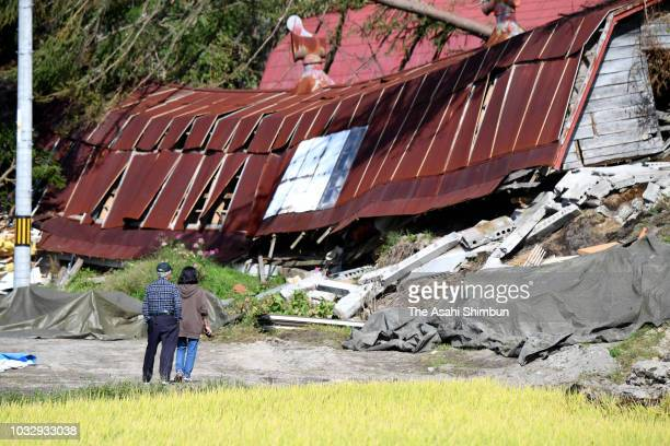 People stand at a destroyed house of their friends a week after the magnitude 67 earthquake on September 13 2018 in Atsuma Hokkaido Japan Concerns...