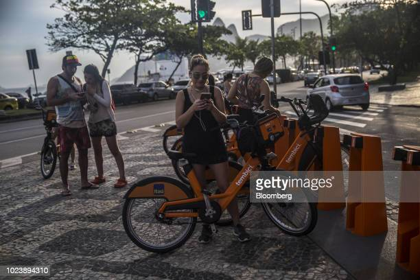 People stand at a Itau Unibanco SA Tembici rental bicycle station on Ipanema Beach in Rio de Janeiro Brazil on Friday Aug 24 2018 As the unemployment...