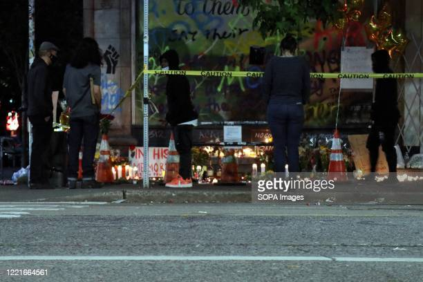 People stand at a makeshift memorial to one of the victims of a June 20 shooting in the Seattles socalled Capitol Hill Autonomous Zone or CHAZ an...