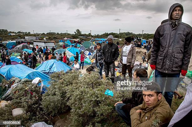 People stand at a site dubbed the 'New Jungle' where some 3000 people have set up camp most seeking desperately to get to England in Calais on...