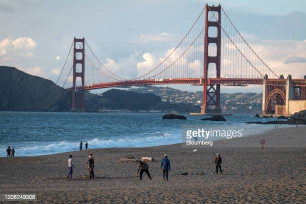 People stand at Baker Beach as the Golden Gate Bridge stands in the background in San Francisco California, U.S., on Wednesday, March 25, 2020....