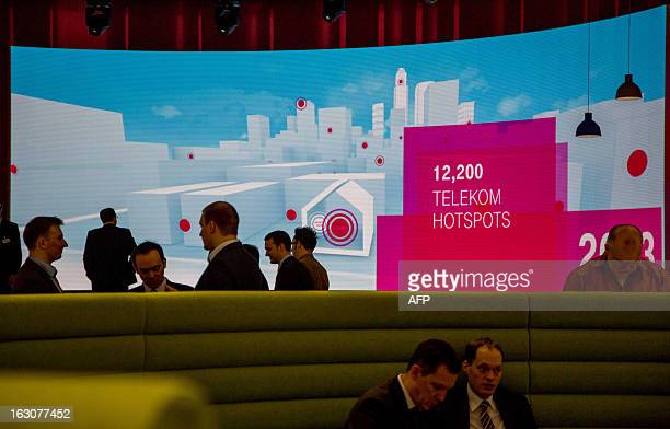 People stand at the booth of German telecommunications giant Deutsche Telekom during the first press day of the CeBIT high-tech fair on March 4, 2013...