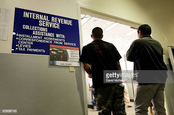 People stand at the door of the local Internal Revenue Service office before going in to get help with their income tax filing on April 15 2005 in...