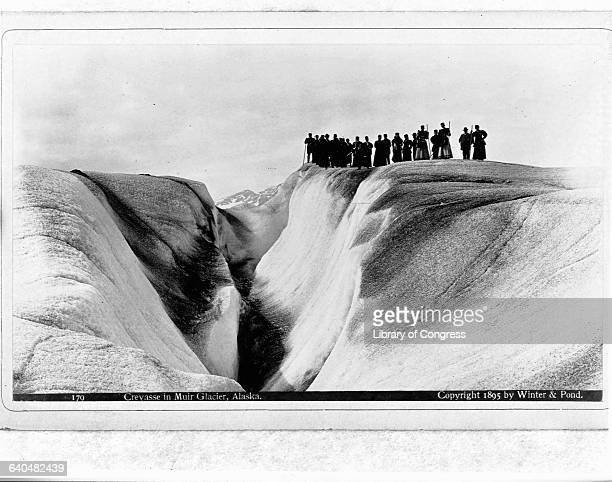 People stand at the edge of a large crevasse in Muir Glcier Alaska 1895 | Location Muir Glacier Alaska USA