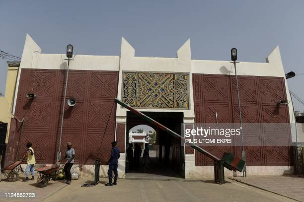 People stand at the gate to Palace of the Emir of Kano Sanusi Lamido Sanusi in Kano on February 14 2019 The Palace of the Emir of Kano Sanusi Lamido...