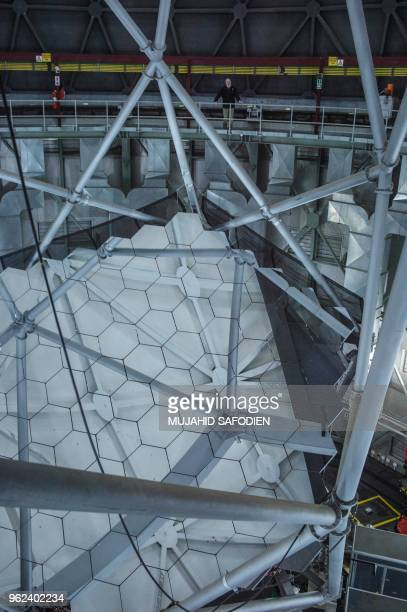 People stand at the mirror of the Southern African Large Telescope on May 25 at the South African Astronomical Observatory near Sutherland where a...