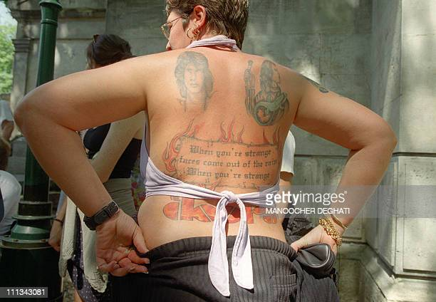 People stand at the Pere Lachaise cemetery in Paris 03 July 2001 to pay respect to 'The Doors' singer US Jim Morrison who died 03 July 1971 in the...