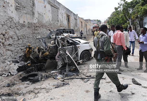 People stand at the site of a major car bomb and gun attack against an intelligence headquarters and detention facility in the center of Mogadishu...