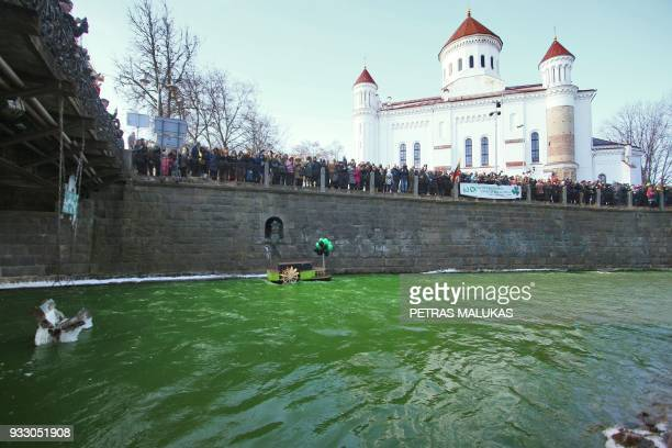 People stand at the Vilnia river that is coloured in green to celebrate the Irish festivity Saint Patrick's Day in Vilnius, Lithuania, on March 17,...
