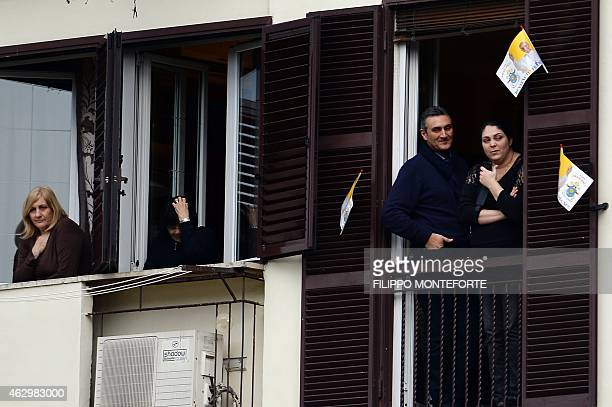People stand at their windows to see Pope Francis during his pastoral visit at the parish of San Michele Arcangelo a Pietralata, on February 8, 2015...