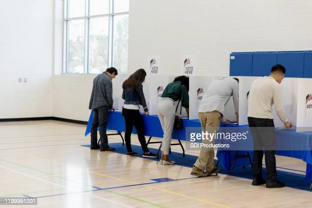 people stand at voting booths along the gym wall - voting booth stock pictures, royalty-free photos & images