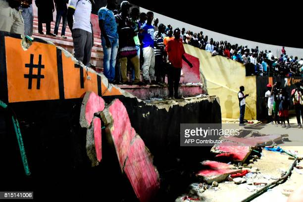 People stand before a collapsed wall at Demba Diop stadium July 15 2017 in Dakar after a football game between local teams Ouakam and Stade de Mbour...