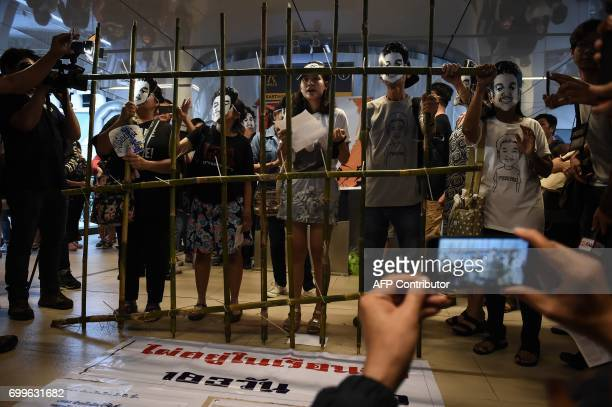 CORRECTION People stand behind makeshift bars wearing masks of Thai human rights activist Jatupat Pai Boonpattararaksa who was arrested in early...