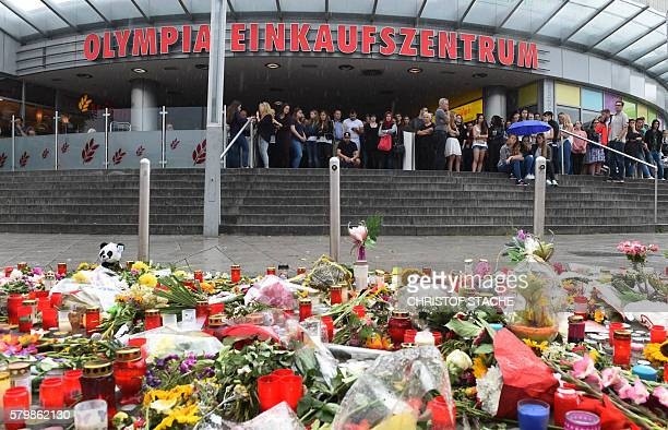 People stand behind of candles and flowers on July 25 2016 in front of the Olympia shopping mall in Munich southern Germany where an 18yearold...