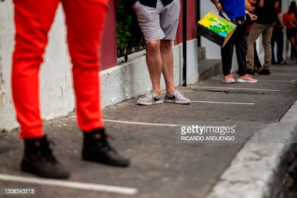 People stand behind tape strips placed on a sidewalk every 6 feet in front of a supermarket that allows only five clients at a time inside to avoid...