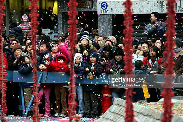 People stand behind thousands of hanging firecrackers during Chinese New Year celebrations at Chatham Square in Chinatown Today marks the beginning...